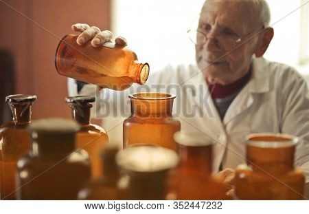 Old chemist working on a compound and making an experiment.