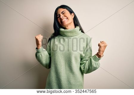 Young beautiful hispanic woman wearing green winter sweater over isolated background very happy and excited doing winner gesture with arms raised, smiling and screaming for success. Celebration
