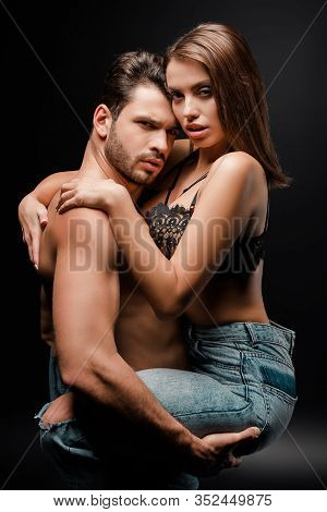 Muscular Man Holding In Arms Woman In Bra And Denim Jeans On Black