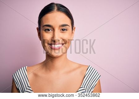 Young beautiful brunette woman wearing casual striped t.shirt over pink background with a happy face standing and smiling with a confident smile showing teeth