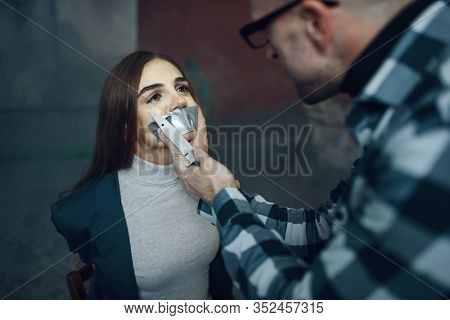 Maniac kidnapper taping his victim's mouth shut