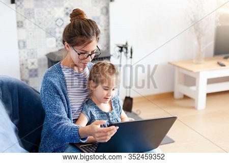 Mother And Daughter Using Laptop And Internet. Freelancer Workplace Home. Woman And Child Girl Sitti