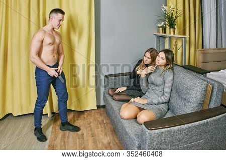 Two Young White Women Are Sitting On The Couch And Watching The Performance Of A Muscular Stripper.