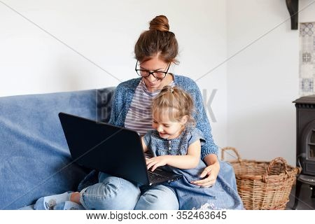 Mother And Daughter Using Laptop And The Internet. Freelancer Workplace Home. Happy Woman Teaching L