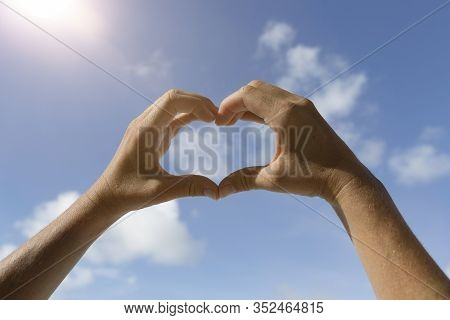 Heart Hands Symbol In Front Of Blue Sunny Sky