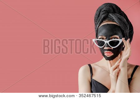 Young Woman In Glasses Appling Black Cosmetic Fabric Facial Mask On Pink Background. Face Peeling Ma