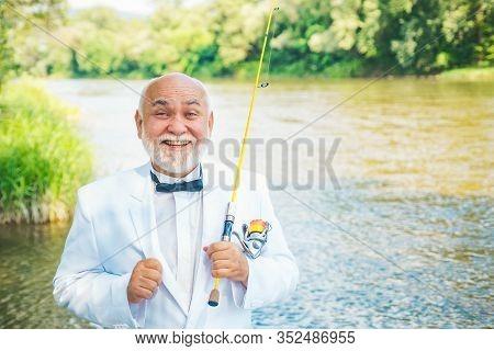 Portrait Of Cheerful Senior Man Fishing. Active Sunny Day. Man Fishing On The Lake. Bearded Man Catc