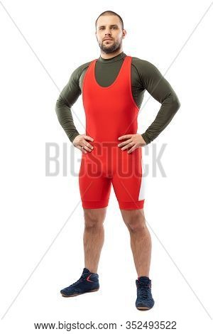 A Strong Strong Young Man In A Sports Red Tights Is Standing With His Hands On His Sides, Looking At