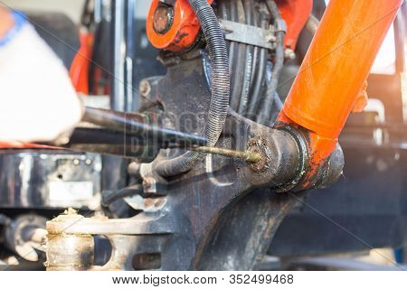 Hand Of A Workman Greasing The Grease Nipple Of A Hydraulic Cylinder The Backhoe. Routine Repair Mai