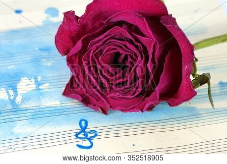 Beautiful Purple Rose On A Music Sheet. Music Sheet In Blue Watercolor Paint And Treble Clef. Music