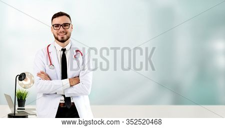 Handsome Doctor Standing In Hospital Office.
