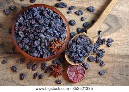 Black Raisins In A Bowl On A Wooden Table. Black Raisins, Dry Citruses And Anise Stars Top View.