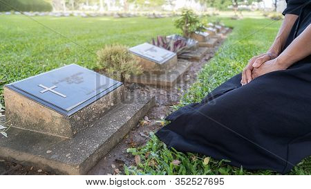 Mourning Young Woman Kneeling At Her Family Grave In Beautiful Green Cemetery. Mourning Concept.