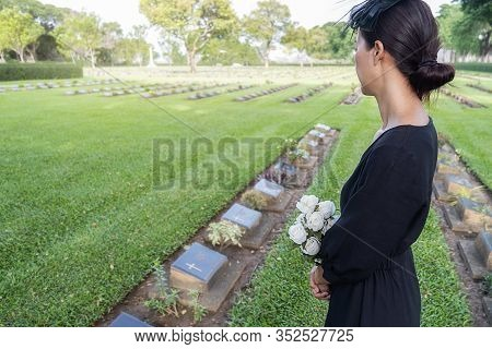 Mourning Young Woman Holding White Flowers At Her Family Grave In Beautiful Green Cemetery.