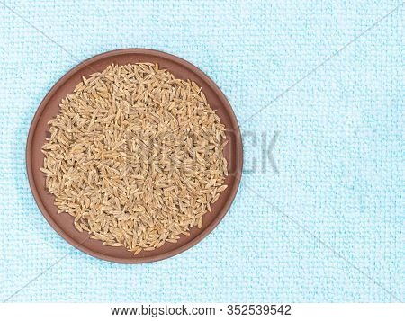 Cumin (jeera) In Clay Plate On Blue Fabric Background