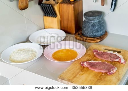 Cooking Pork Homemade Cutlet In Kitchen, Pork Chop On Chopping Board , And Ingredient Powder And Egg
