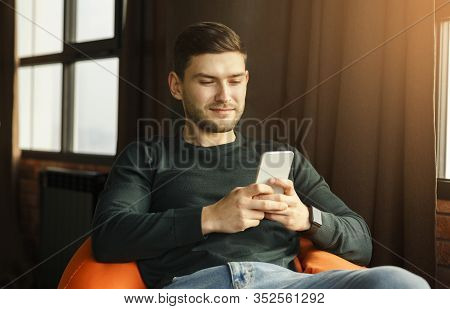 Mobile App. Student Guy Using Phone Texting And Browsing Internet Sitting In Beanbag Chair Indoor. S
