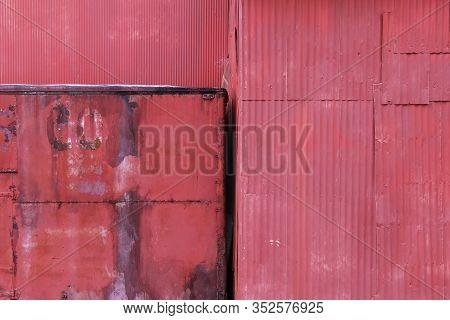 A Rusty Old Red Painted Wall Of Abandoned Metal Building In A Farm Yard