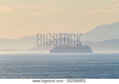 Cruise liner ship silhouette in haze in Mediterranea sea. Aegean sea, Greece