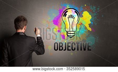 businessman drawing colorful light bulb with OBJECTIVE inscription on textured concrete wall, new business idea concept