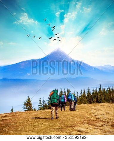 Tourists hiking in mountains with backpacks on summer day. The concept of travel, adventure or expedition in the mountains.