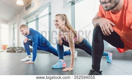 Group of three people in gym fitness class stretching