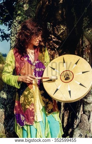 Beautiful Shamanic Girl Playing On Shaman Frame Drum In The Nature.