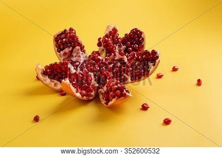 Juicy Pomegranate Closeup. Opened Pomegranate Fruit. Pomegranate On A Yellow Background. Ripe Open P