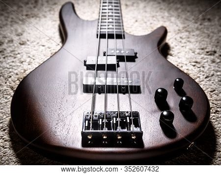 Bass Electric Guitar With Four Strings Closeup. Popular Rock Musical Instrument. Close View Of Brown