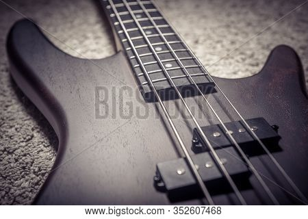 Bass Guitar With Four Strings Closeup. Detail Of Popular Rock Musical Instrument. Close View Of Brow