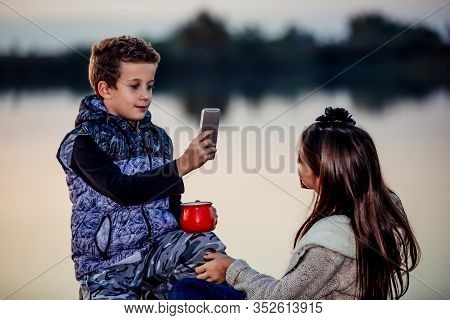 Boy Taking A Photo With Phone Of His Friend While Sitting By The Lake In The Evening.