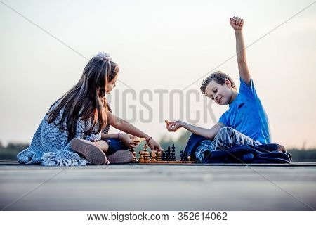 Two Cute Little Boy And Girl Having Fun While Playing Chess Sitting By The Lake In The Evening.