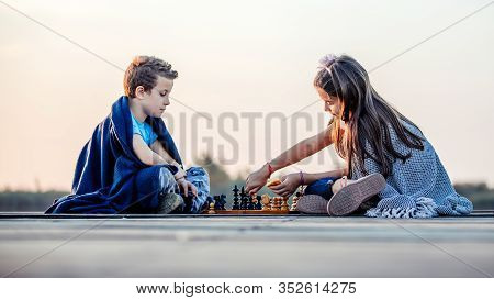 Two Young Cute Little Friends, Boy And Girl Having Fun While Playing Chess Sitting Covered With Blan
