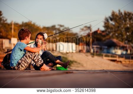 Two Young Cute Little Friends, Boy And Girl Talking, Eating Sandwiches And Fishing On A Lake In A Su