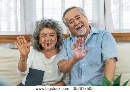 Asian Couple Grandparent Greeting And Talking With Granddaughter With Happy Feeling Via Video Phone