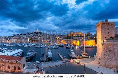 Night Old Port With Forts Saint-jean And Saint-nicolas, The Basilica Of Notre Dame De La Garde On Th