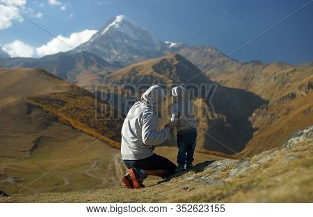 Little Boy With Father Looking At Incredible Snowy Mount Glacier And Brown Hills At Autumn Time. Tra