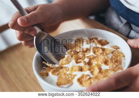 Detail Of The Hands Of A Little Girl Holding A Spoon And A Bowl With Cereal And Milk For Breakfast.