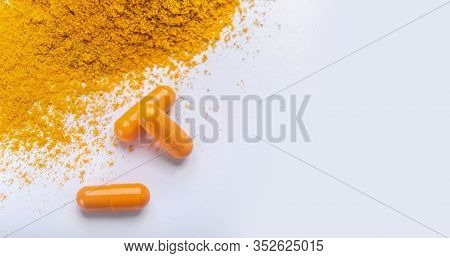 Supplement Pills Of Curcumin Or Turmeric With A Heap Of The In Dry Powder, Gray Background, Copy Spa