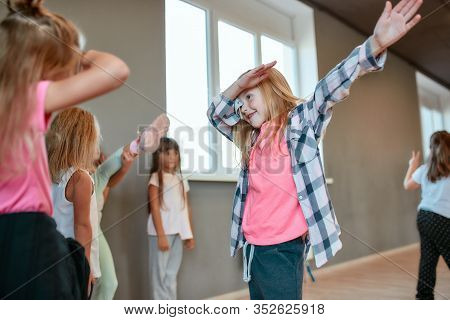 Portrait Of A Little Happy Girl Gesturing And Having Fun While Having A Choreography Class. Group Of