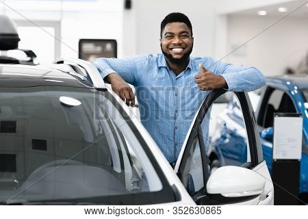 Great Car. Cheerful African American Guy Standing Near Auto Gesturing Thumbs Up Buying Vehicle In De