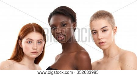 Beautiful Multicultural Young Girls Looking At Camera While Posing In Studio Over White Background.