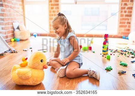 Young beautiful blonde girl kid enjoying play school with toys at kindergarten, smiling happy playing with stuffed animal at home
