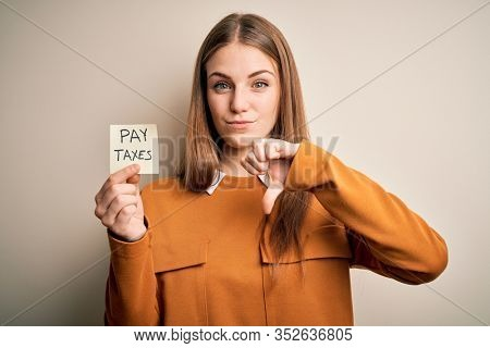 Young beautiful blonde woman holding pay taxes to goverment reminder over yellow background with angry face, negative sign showing dislike with thumbs down, rejection concept