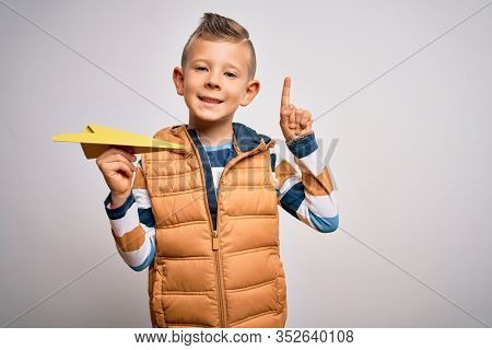 Young little caucasian kid having fun and playing imagination fly with paper plane surprised with an idea or question pointing finger with happy face, number one
