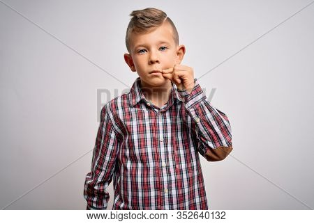 Young little caucasian kid with blue eyes wearing elegant shirt standing over isolated background mouth and lips shut as zip with fingers. Secret and silent, taboo talking