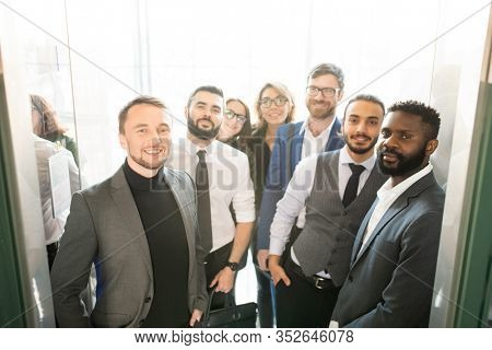 Multi-ethnic group of business specialists in stylish formal outfits standing in entrance and looking at camera