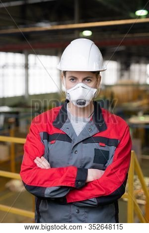 Portrait of construction worker in respirator and hardhat standing with crossed arms at building site
