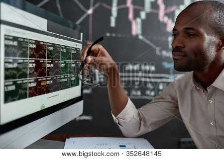 African Businessman, Trader Sitting In Front Of Computer Screen And Holding Glasses While Looking At