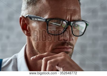 Close Up Of Middle-aged Caucasian Trader In Glasses Looking Focused While Working In The Office. Sto